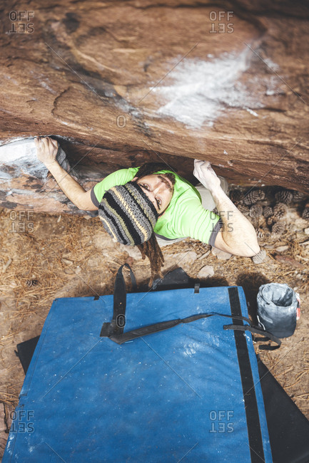 Rock climber contemplating next move on boulder problem