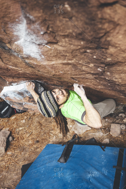 Rock climber grimacing with effort on boulder problem