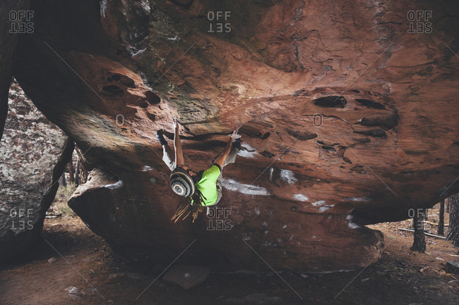 Rock climber contemplating next move on overhanging boulder problem