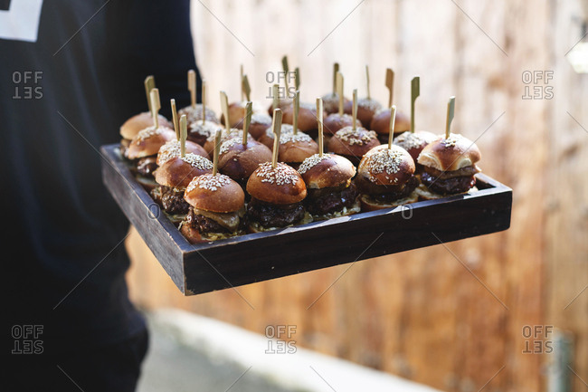 Server carrying tray of mini foie gras burgers