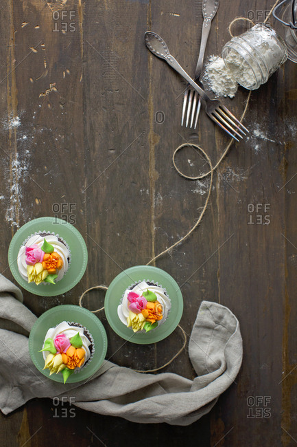 Overhead view of cupcakes decorated with sugar flowers and upended jar of powdered sugar