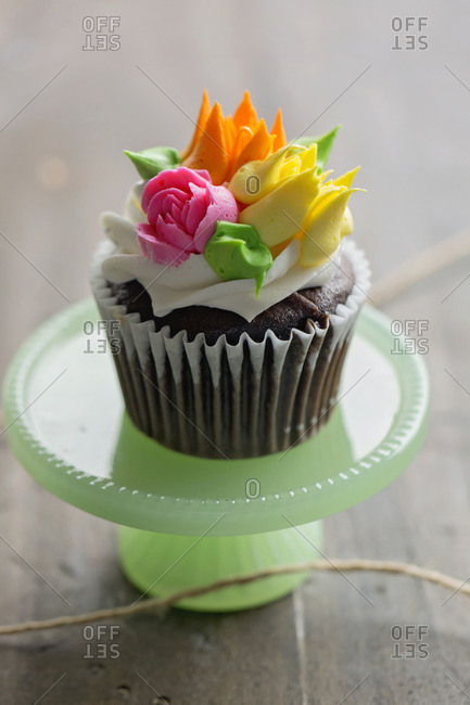 High angle view of single chocolate cupcake decorated with sugar flowers