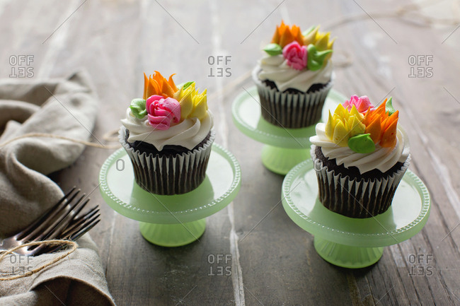 High angle view of chocolate cupcakes decorated with sugar flowers