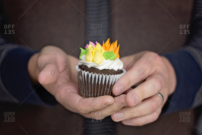Woman holding single chocolate cupcake decorated with sugar flowers