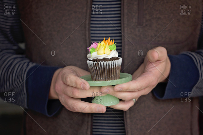 Woman holding single chocolate cupcake on stand decorated with sugar flowers