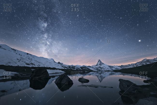 Milky way over Matterhorn Mountain with reflection in Stellisee Lake, Switzerland