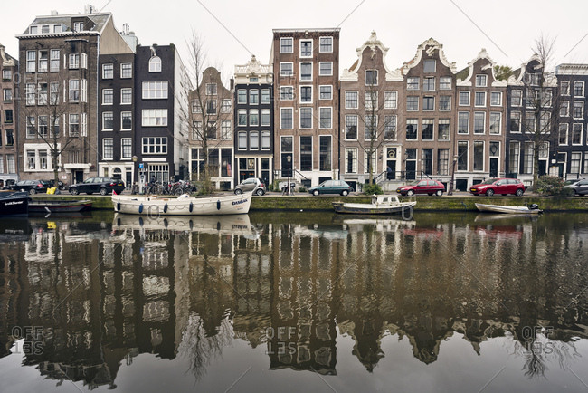 Amsterdam, Holland - February 14, 2018: Reflection of boats and row houses in Amsterdam canal