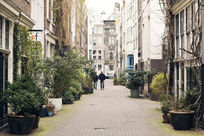 Amsterdam, Holland - February 14, 2018: Men walking down street in Amsterdam