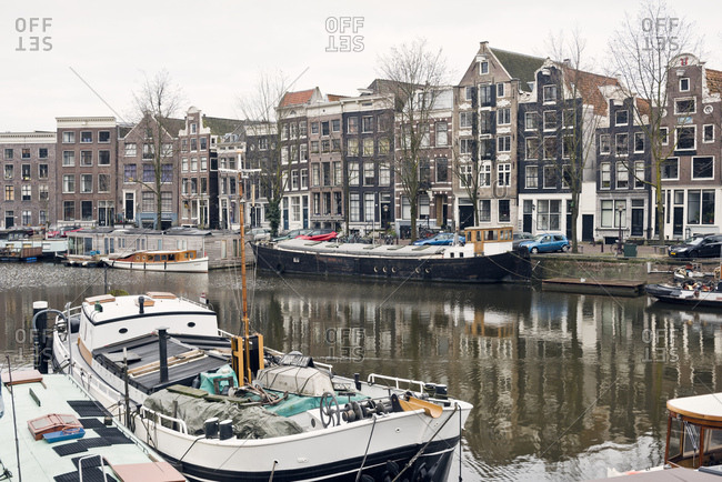 Amsterdam, Holland - February 14, 2018: Reflection of buildings and boats in a canal in Amsterdam