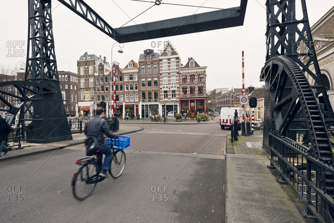 Amsterdam, Holland - February 14, 2018: Man riding bicycle over bridge in Amsterdam