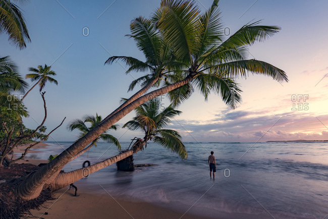 Man on a deserted beach at sunrise on the Caribbean island of Puerto Rico