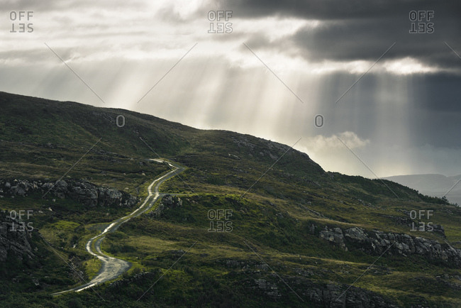 Winding dirt road on Ireland's west coast with sunbeams, Donegal, Ireland