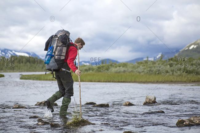 Hiker crossing a river in Sarek National Park, Sweden