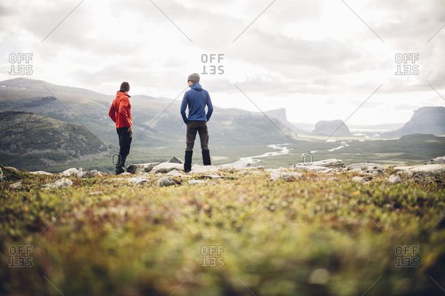 Two male hikers enjoys the view over the Rapadalen delta in Sarek National Park, Sweden