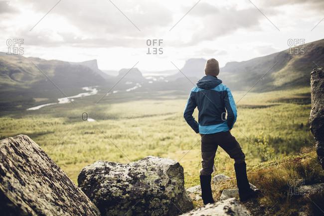 Male hiker enjoys the view over the Rapadalen delta in Sarek National Park, Sweden