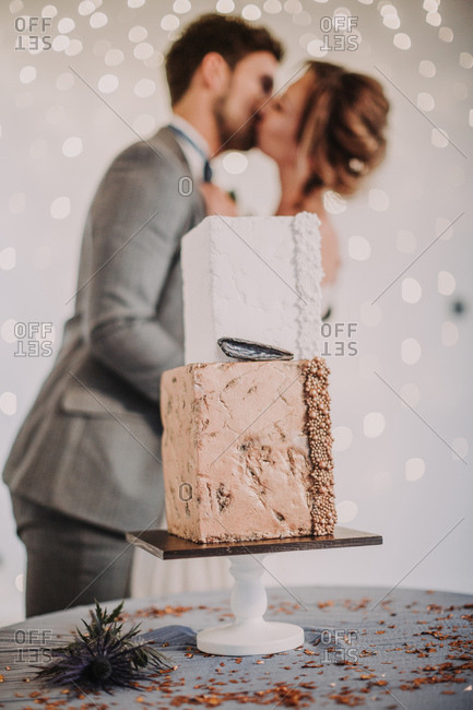 Married couple kissing behind table with wedding cake