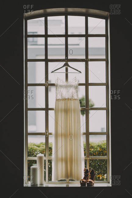 Wedding dress hanging in window beside shoes and candles