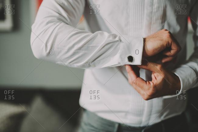 Man puts cufflinks on his shirt
