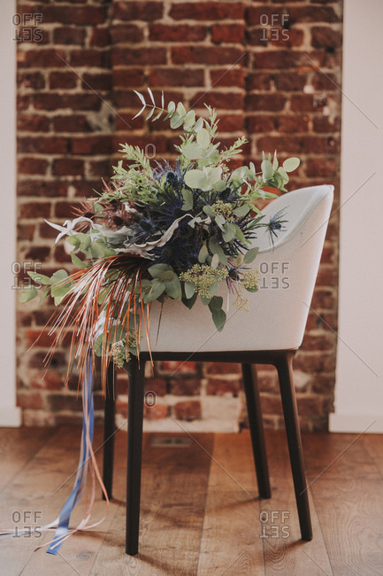 Bouquet on a chair in front of brick wall
