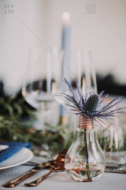 Wedding reception table with a light bulb and thistle decoration