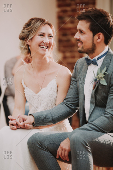 Bride and groom holding hands and smiling
