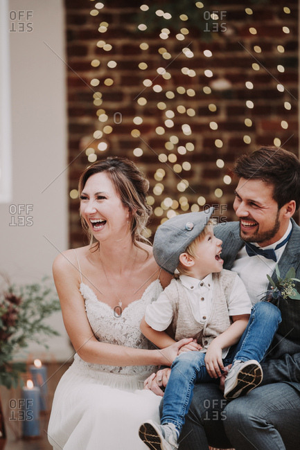 Bridal couple and boy sitting and laughing