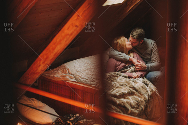 Young couple kissing on sofa in an attic
