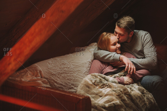 Man kissing young woman's forehead on sofa in an attic
