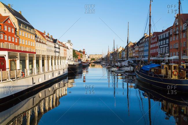 September 10, 2017: Moored restaurant boat and colorful 17th century town houses on Nyhavn canal, Copenhagen, Denmark