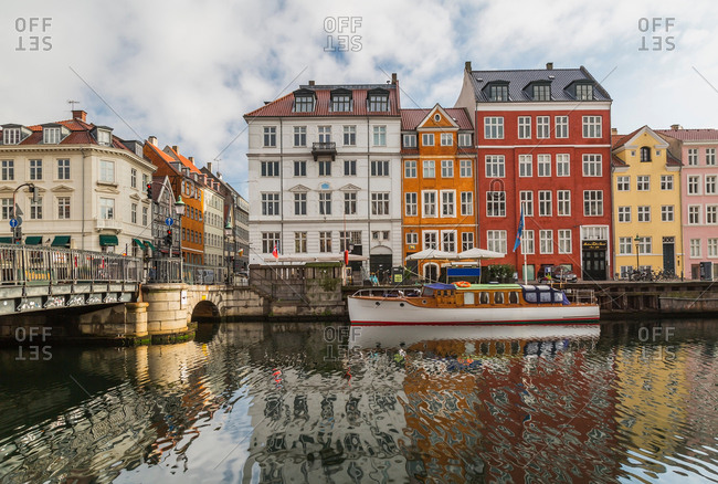 September 10, 2017: Moored boat and bridge with colorful 17th century town houses on Nyhavn canal, Copenhagen, Denmark