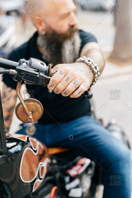 Mature male hipster astride motorcycle, close up of tattooed hand