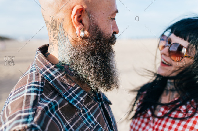 Happy hipster couple face to face on beach, Valencia, Spain