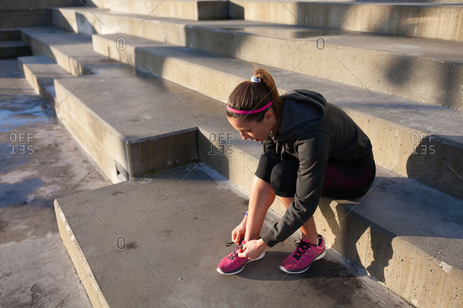 Young woman tying shoelace on training shoe, stretching legs