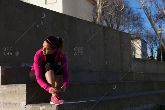 Young woman tying shoelace on training shoe, stretching legs