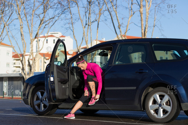 Young woman in car tying shoelace on training shoe, stretching legs