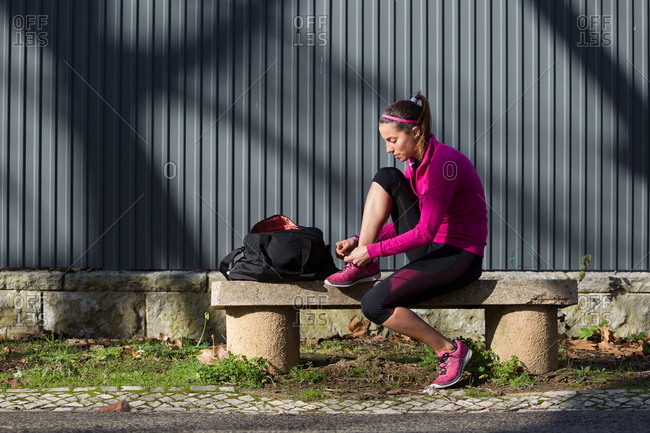 Young woman on bench tying shoelace on training shoe