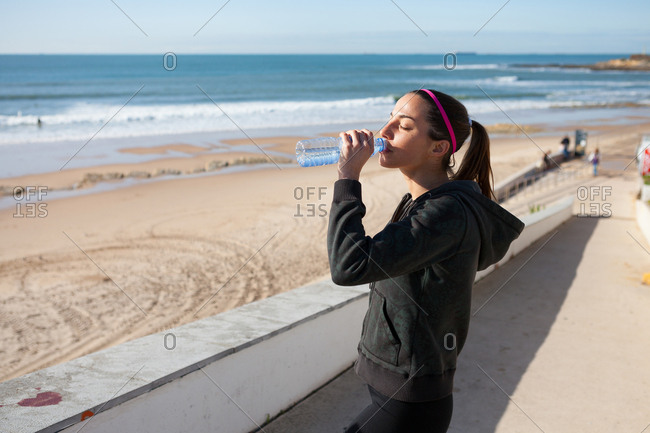 Young woman at beach drinking water from water bottle, Carcavelos, Lisboan, Portugal, Europe