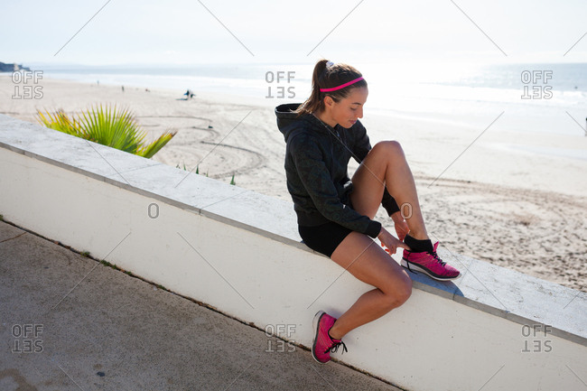 Young woman at beach putting on training shoe, Carcavelos, Lisboan, Portugal, Europe