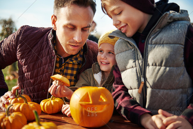 Man with son and daughter looking at carved halloween pumpkin at pumpkin patch