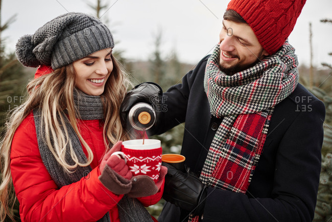 Young couple pouring coffee while shopping for christmas tree from forest