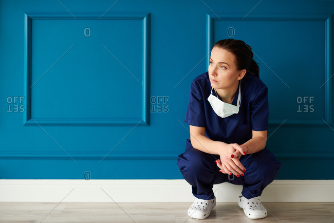 Portrait of female surgeon, crouching, looking away, pensive expression