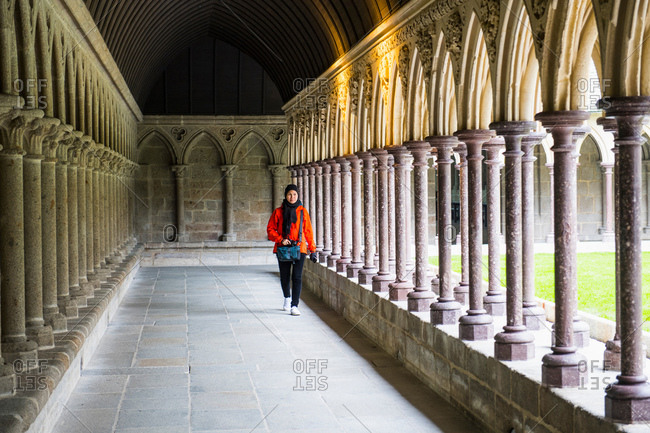 Female tourist strolling in Abbey cloister of Mont Saint-Michel, France