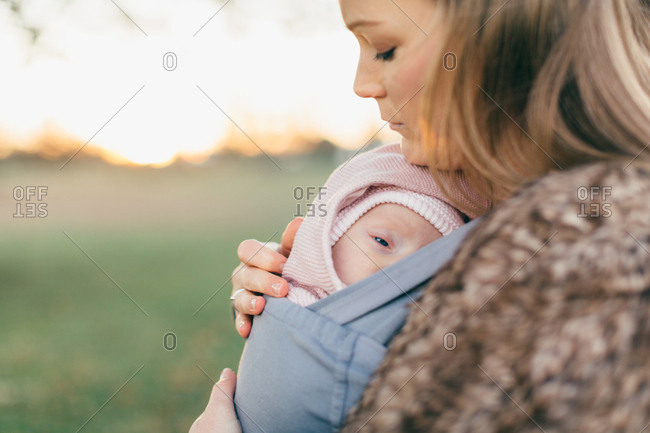Mother and baby daughter outdoors, mother carrying baby in baby sling