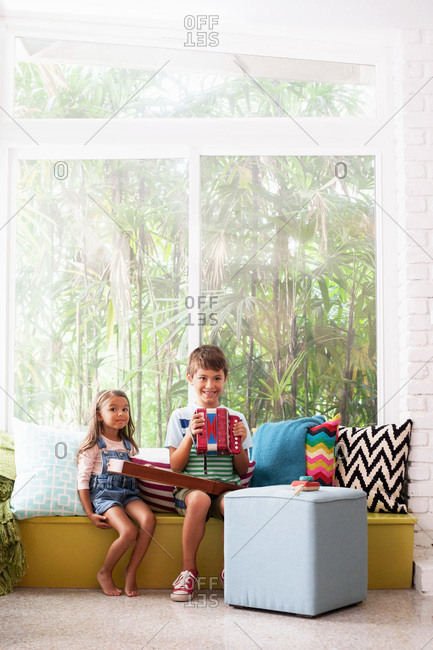 Portrait of girl on window seat with boy practicing accordion