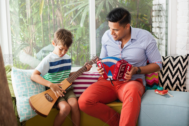 Boy playing guitar with music teacher on window seat