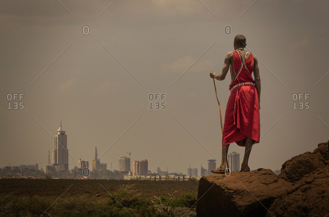 Masai man with traditional dress watching Nairobi's skyline, Nairobi, Nairobi Area, Kenya