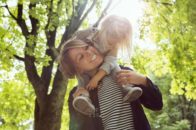 Mother giving toddler daughter shoulder carry in sunlit park