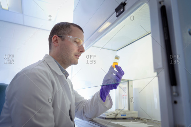 Scientist inspecting pharmaceutical sample in fume cupboard in laboratory