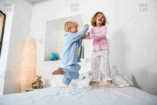Female and male twins jumping together on bed