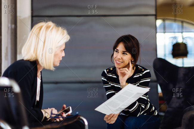 Two businesswomen in meeting, looking at document